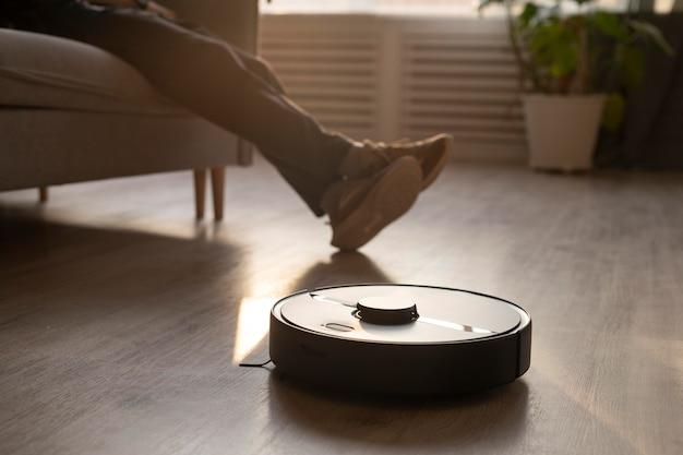 Человек с помощью робота-пылесоса в гостиной