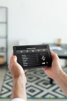 Человек, использующий умный домашний планшет в помещении