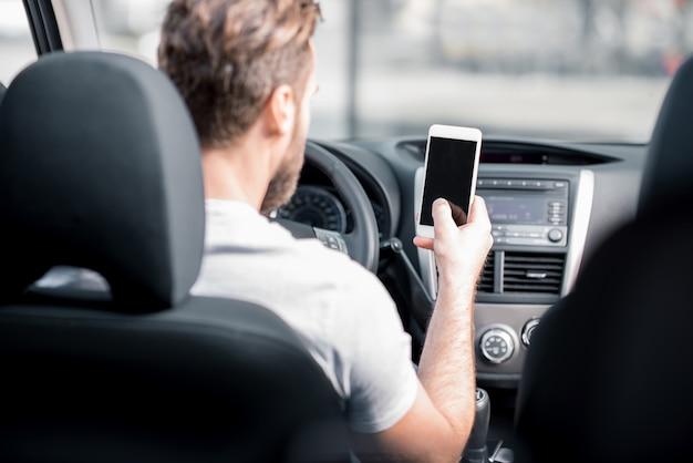 자동차 앞 좌석에 앉아 스마트 폰을 사용하는 남자. 빈 화면이 있는 전화기에 초점을 맞춘 후면 보기