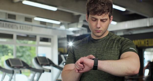 체육관에서 스마트 시계를 사용하는 남자. 운동을 좋아하는 남자는 체육관 운동, 피트니스 기술 후 스마트워치에서 맥박을 확인합니다. 스포츠, 피트니스, 건강 관리 개념입니다.