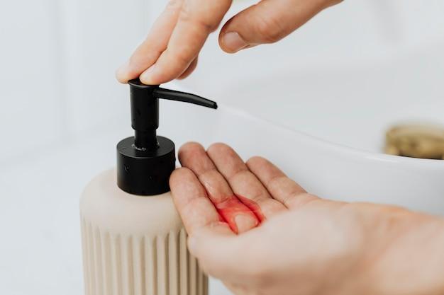 石鹸ディスペンサーを使う男性