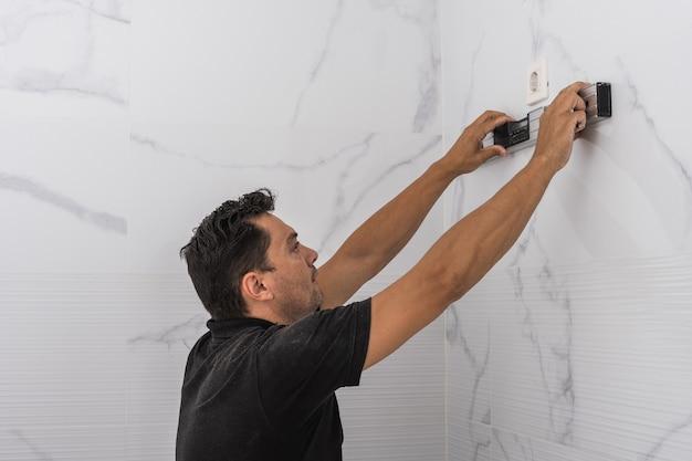 台所の壁に水準器を使用している男