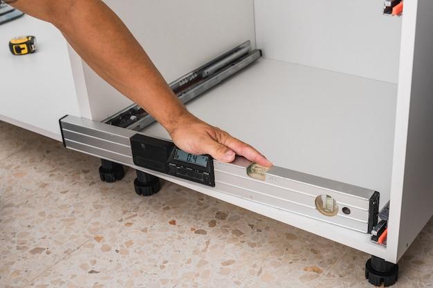 水準器を使用して家具の設置を確認する男性