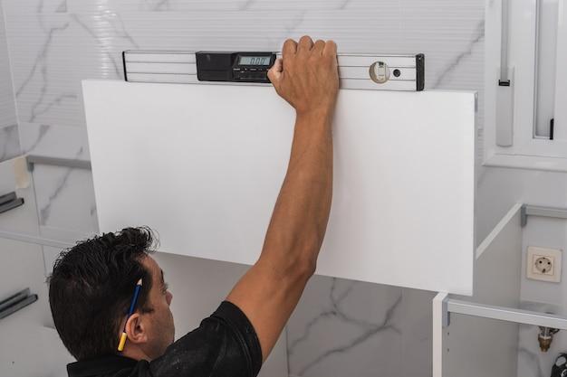 水準器を使用してキッチンユニットを設置する男性