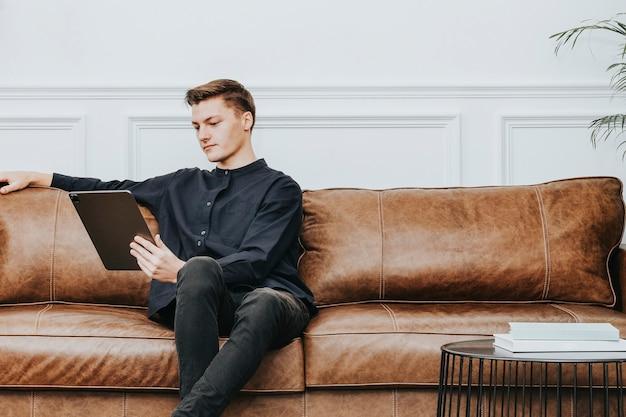タブレットを使用して自宅で仕事をしている男性