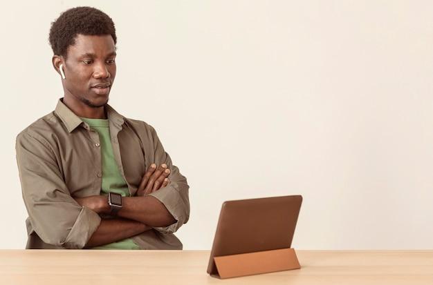 Uomo che utilizza aria baccelli e guardando la tavoletta digitale
