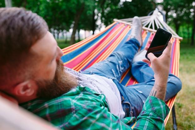 Человек с помощью приложения на своем мобильном телефоне белый качается в гамаке