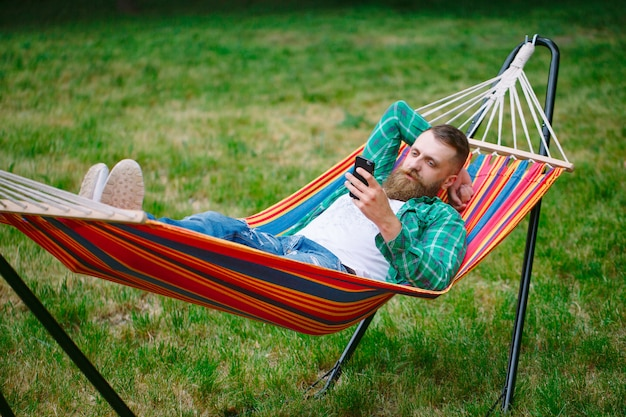 Man using an app on his mobile phone white swinging in a hammock