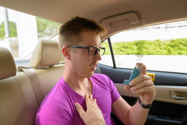 Man using asthma inhaler in back seat of car