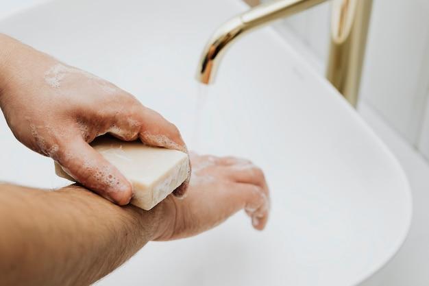 Uomo che usa una saponetta per lavarsi le mani