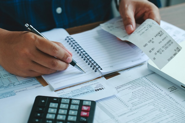 使用している人は、オフィスやビジネスの仕事のバックグラウンドで木製の机の上に国内の請求書を計算