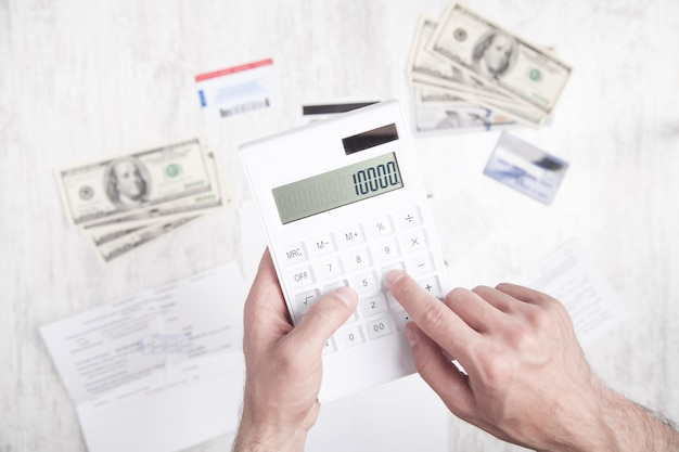 電卓を使用している男。ドル、クレジットカード、机の上の書類