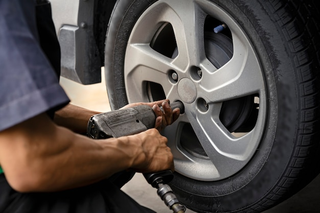 Man using car mechanic block the wind wheel.     to check your tires and brake for car.auto mechanic preparing for the work.