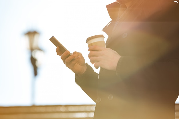 Man using cell phone and drinking coffee outdoors in sunny day
