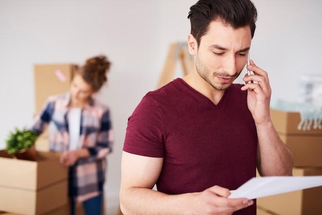 Человек, использующий мобильный телефон в своем новом доме