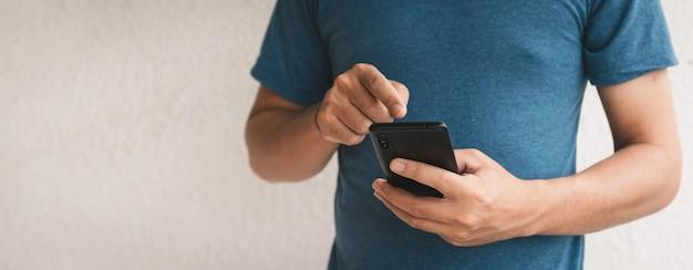Человек, использующий мобильный телефон для поиска данных и социальных сетей в интернете