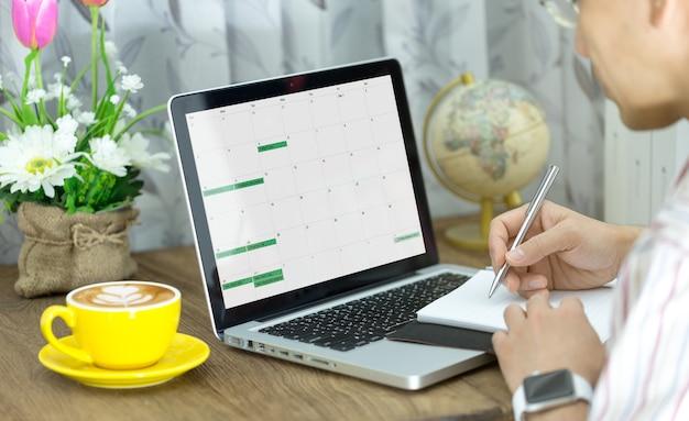 コンピューターのラップトップとノートブックを使用している男性は、テーブルの上にコーヒーを入れてカレンダーと計画を参照してください