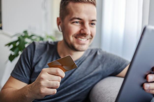 집에 앉아있는 동안 온라인 쇼핑을 위해 신용 카드와 태블릿을 사용하는 사람