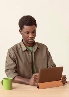 デジタルタブレットを使用し、マグカップを持っている男