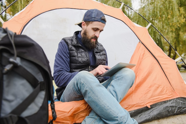 Man using digital tablet in camping tent