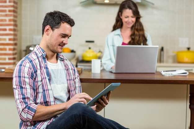 Man using digital tablet in kitchen while woman using laptop in background