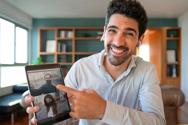 Человек с помощью цифрового планшета во время видеозвонка со своими друзьями, оставаясь дома.