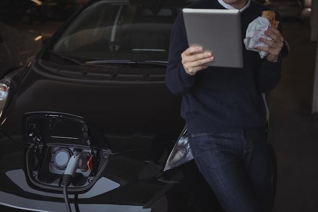 Uomo che utilizza la tavoletta digitale durante la ricarica dell'auto elettrica