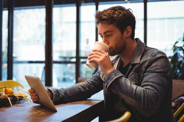 커피를 마시면서 디지털 태블릿을 사용하는 사람
