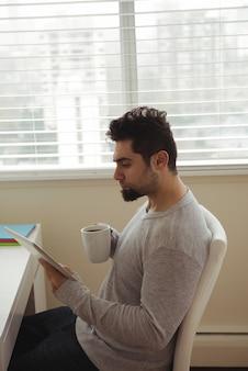 コーヒーを飲みながらデジタルタブレットを使用する男