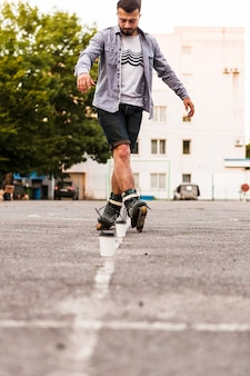 Man using disposal cup while practicing rollerskate
