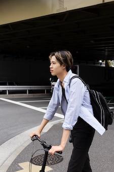 Человек, использующий электрический велосипед в городе