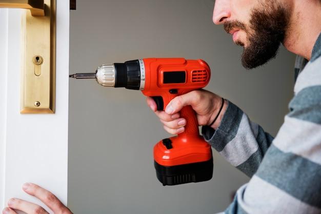 Man using electronic drill install door