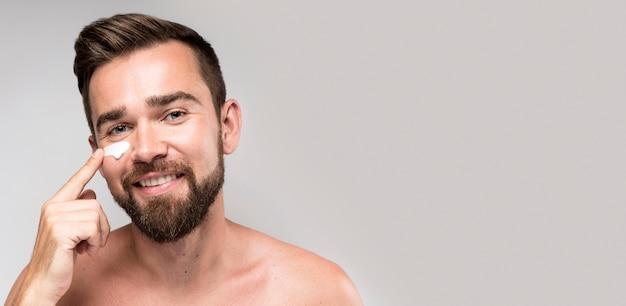 Uomo che utilizza crema per il viso con copia spazio