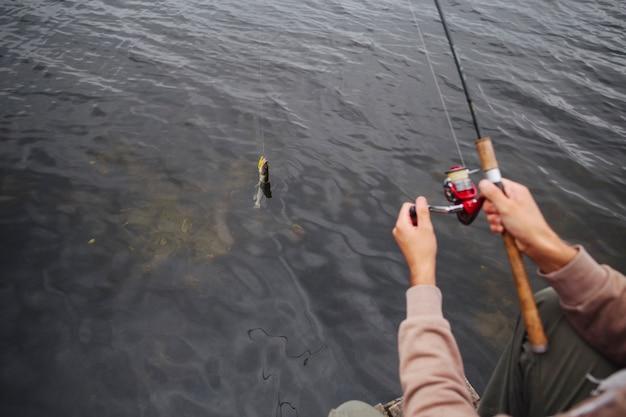 Человек, используя рыболовную катушку, чтобы поймать рыбу из озера