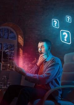 남자는 가제트를 사용하고 밤에 집에서 네온 알림을 받습니다. 안락의자에 앉아 인터넷을 검색하고 정보를 찾고 있습니다. 소셜 미디어 남용, 채팅 및 탐색, 가제트 중독.
