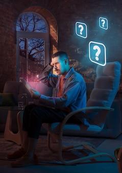 Человек, использующий гаджет и получающий неоновые уведомления дома ночью