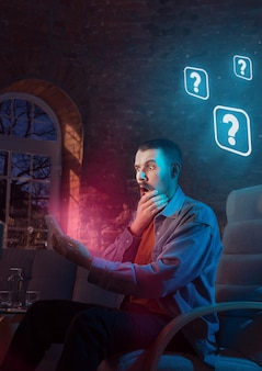 Man using gadget and receive neon notifications at home at night. sitting on armchair, serfing in internet and looking for information. social media abusing, chatting and browsing, gadget addiction.