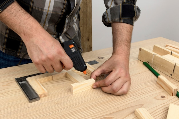 Man using glue on wood carpentry workshop concept