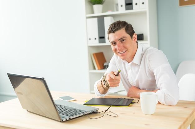 Человек, использующий графический планшет в офисе и смотрящий на вас