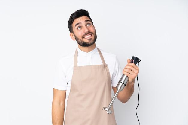 Человек, использующий ручной блендер, изолированный на белой стене, смеется и смотрит вверх