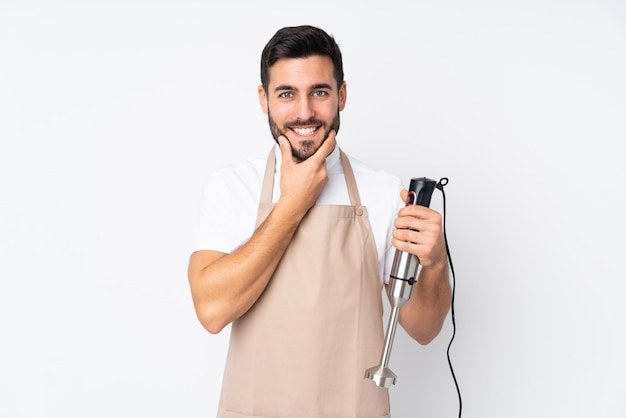 Man using hand blender isolated on white wall laughing