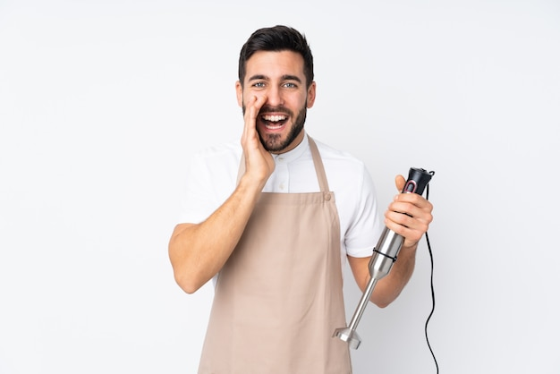 Man using hand blender isolated on white wall shouting with mouth wide open
