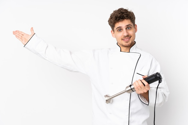 Man using hand blender on white wall extending hands to the side for inviting to come