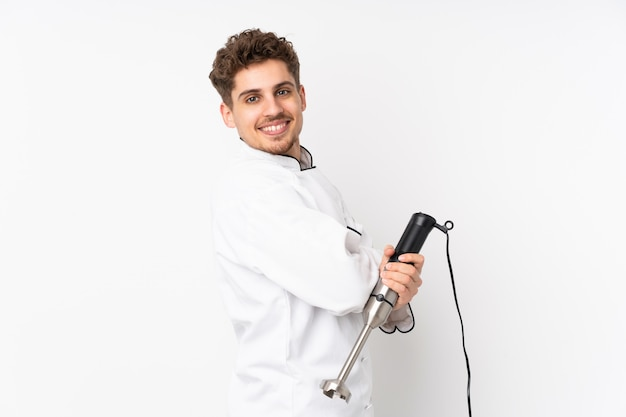 Man using hand blender on white wall laughing