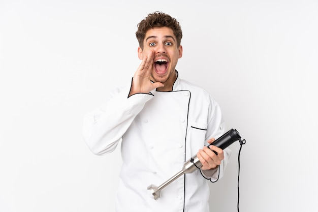 Man using hand blender on white wall shouting with mouth wide open