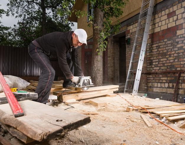 집 건설을 위해 나무 판자를 자르기 위해 휴대용 전동 톱을 사용하는 남자 바닥에 톱밥 더미를 남기고