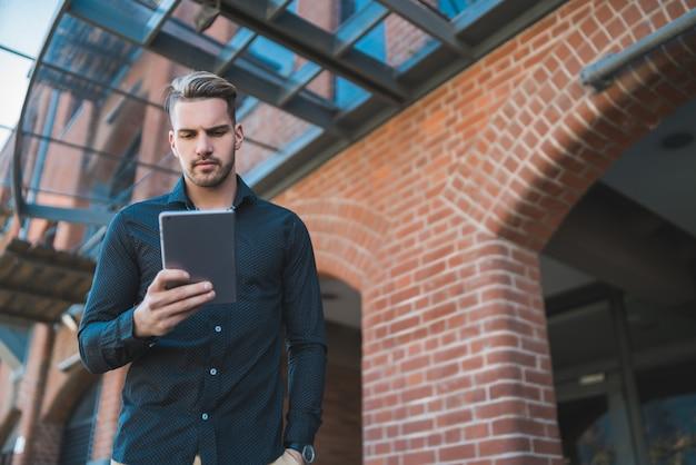 Человек с помощью своего цифрового планшета на открытом воздухе.