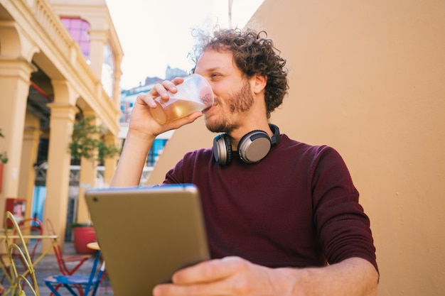 Man using his digital tablet while drinking beer.