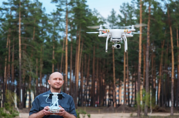Man using his drone outdoor with forest