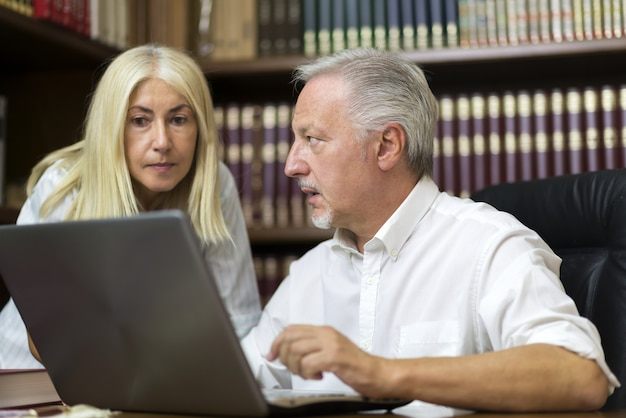 Man using his laptop while talking to a woman
